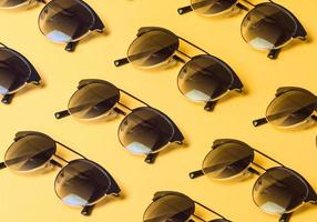 Pattern of sunglasses over a pastel yellow background with copy space photo
