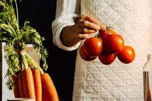 Woman holding tomatoes and vegetables over a table with water photo