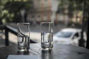 Two glasses of water stand on a table in a restaurant on the background of city streets photo