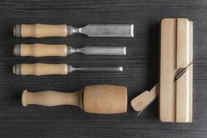 Cinceles y mazo de madera y plano sobre un fondo negro taller de carpintería foto