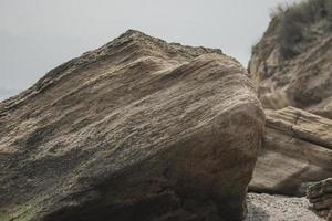 large sea boulders lie on the beach photo