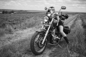brunette biker on a motorcycle in black leather jacket lavender field against the sky with clouds photo
