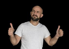 white bald man with a beard in a white T shirt keeps fingers up photo