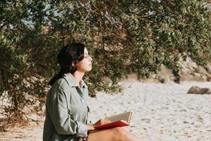 Joven mujer marroquí en ropa moderna sentada en la playa leyendo un libro foto