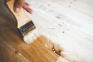 Aplicar pintura barniz sobre una superficie de madera. foto