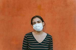 Retrato de una mujer delante de una pared roja sonriendo a la cámara foto