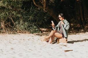 Joven mujer marroquí en ropa moderna y gafas de sol sentado en la playa foto