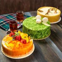 Different beautiful macaron cakes on the wooden table with tea photo