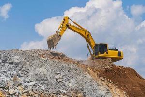 Excavadora trabajando al aire libre bajo un cielo azul foto