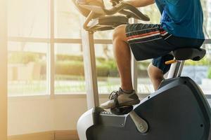 Cerca de un hombre ejercicio en el gimnasio en bicicleta en bicicleta en el gimnasio foto