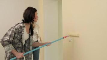 Two Young Ladies Painting a Wall with a Roller video