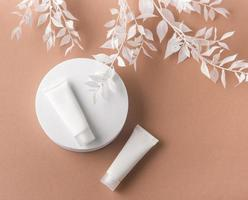 White tubes of cream on a brown background photo