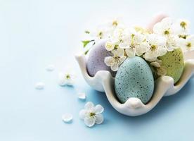 huevos de pascua en bandeja de huevos y flor de primavera foto