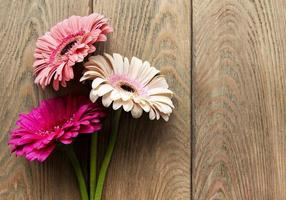 Bright gerbera flowers on a old wooden background photo