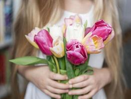 Spring tulips in the hands of a little girl. photo