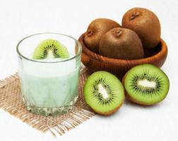 Kiwi smoothie in a glass on an old white wooden background photo