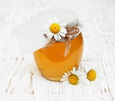 tarro de miel con flores de manzanilla foto