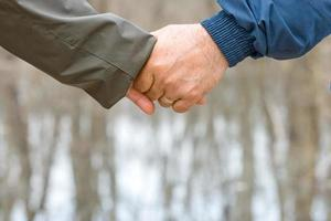 Couple holding hands on abstract blurred background with copy space photo