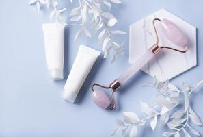 Cosmetic products, cream tubes, and a face roller on a blue background photo