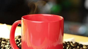 Tasse à café avec fumée de vapeur naturelle de café sur fond de grains de café torréfiés frais sur la table le matin video
