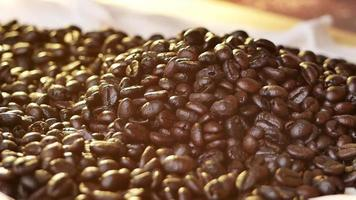 Fresh roasted coffee beans falling on a bag rag surface video