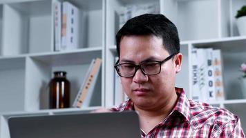 Portrait asiatique lunettes homme à la recherche d'écran moniteur avec visage stressé au bureau à domicile en période de quarantaine mâle à l'aide et en tapant sur ordinateur portable avec fond d'étagère de livre video