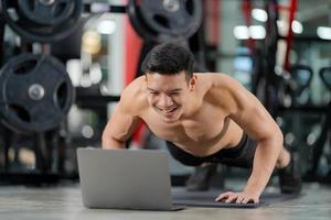 Formación en línea deporte hombre entrenamiento haciendo flexiones ejercicio con portátil en el gimnasio foto