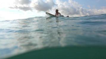 surfare paddlar i havet och stänker kameran video