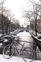 Bicicleta y canal en Amsterdam en la nieve. foto