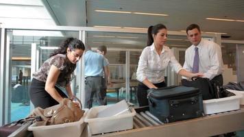 los viajeros del aeropuerto recogen sus pertenencias después del control de equipaje video