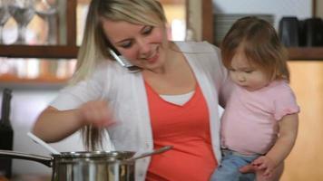 Mutter mit Baby in der Küche Multitasking video