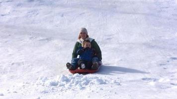 mor och son ridning släde, slow motion video