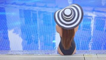 asiatisk kvinna med en stor hatt sitter vid poolen video