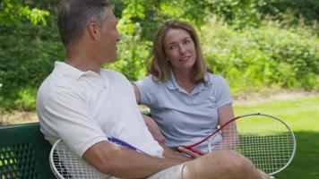 ouder paar buitenshuis nemen een pauze van het tennissen video