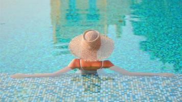 kvinna i en stråhatt njuta av en pool video