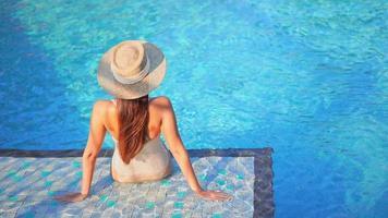 en kvinna som sitter i solen nära en pool video