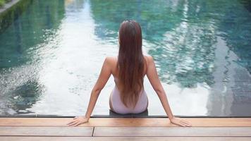 kvinna som sitter framför poolen video