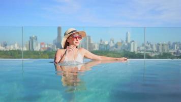 kvinna som kopplar av i en pool framför en stadsbild video