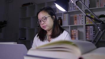 Mulher asiática estressada trabalhando em um laptop à noite em casa mulher se concentrando no computador para fazer relatório de projeto especial pesquisando informações na internet trabalhando duro video