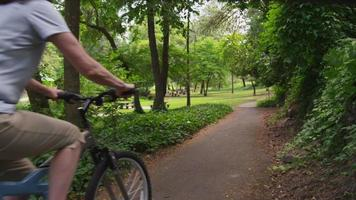 Mature couple riding bicycles through park video
