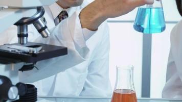 Scientists in lab looking at beaker of liquid video
