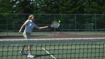 rijpe vrouw raakt tennisbal, slow-motion video