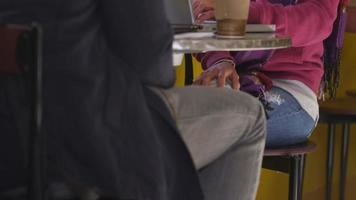 College students in cafe talking and drinking coffee together video