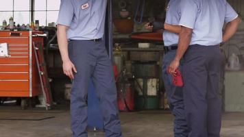 drie automonteurs kijken samen naar auto video