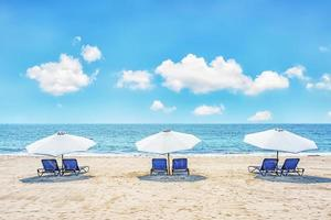 Chairs and umbrellas on a tropical beach photo