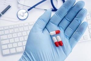Mano humana en guante protector sosteniendo pastillas y escritorio médico en concepto de medicina o medicamento de fondo foto