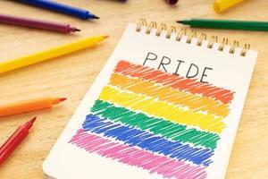 Cuaderno con dibujo de la bandera del arco iris lgbt y rotuladores en la mesa de madera foto