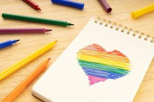 Notebook with LGBT rainbow flag heart shaped drawing and marker pens on wooden table photo