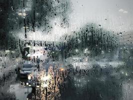 Raindrop on glass window in rainy season rain background photo