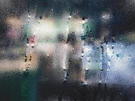 Raindrop on glass window in rainy season at cafe photo